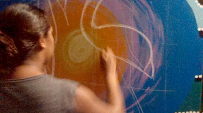 Kirra Webb working on the mural.